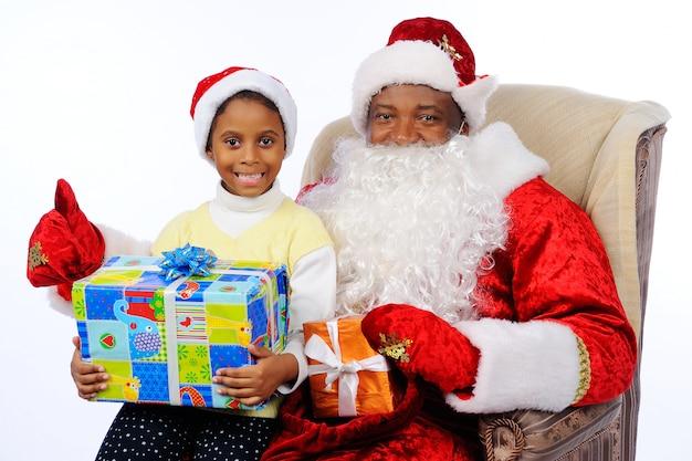 Een zwarte man, een afrikaanse amerikaan in het kostuum van de kerstman, zit in een stoel.