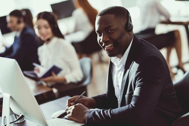 Een zwarte man werkt in een callcenter.