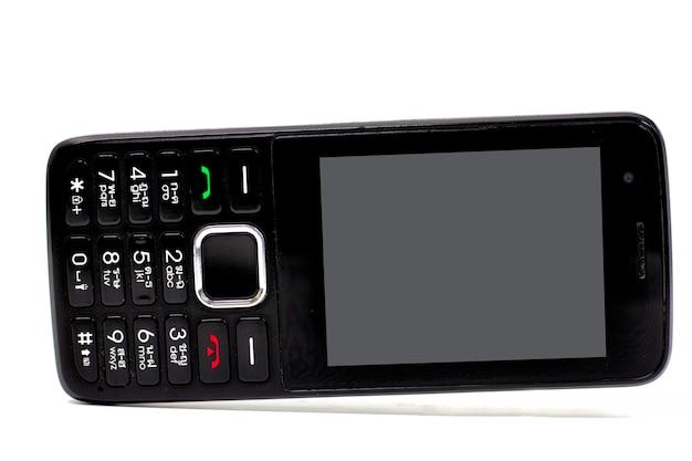 Een zwarte oude telefoon is gekanteld tegen geïsoleerd op wit