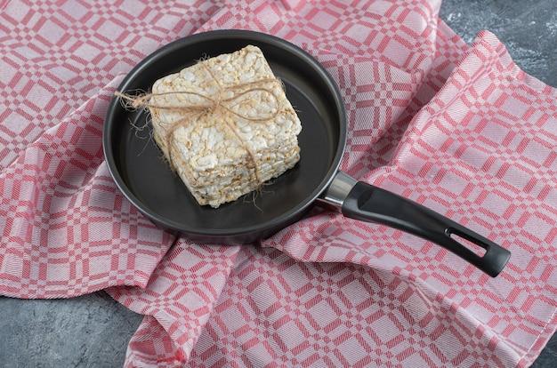 Een zwarte pan vol gepofte rijstbrood op een tafelkleed.