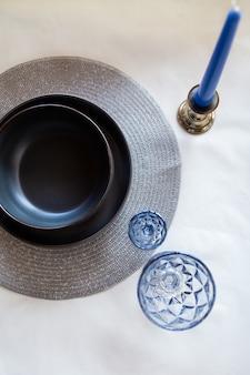 Een zwarte plaat met blauwe glazen en kaarsen. mooie tafel setting