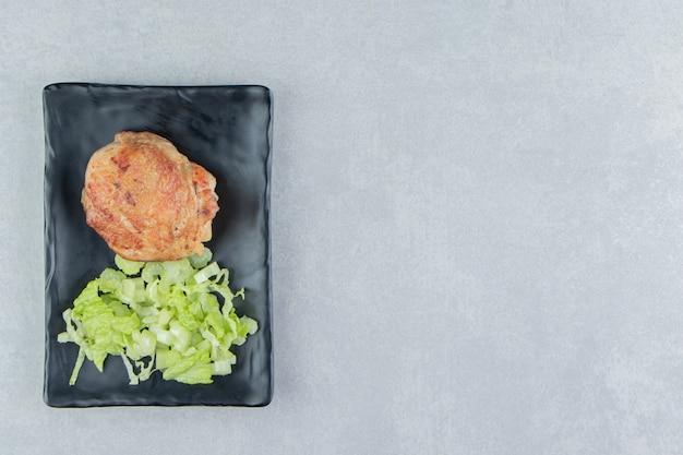 Een zwarte plaat met gebakken vlees en groentesalade.