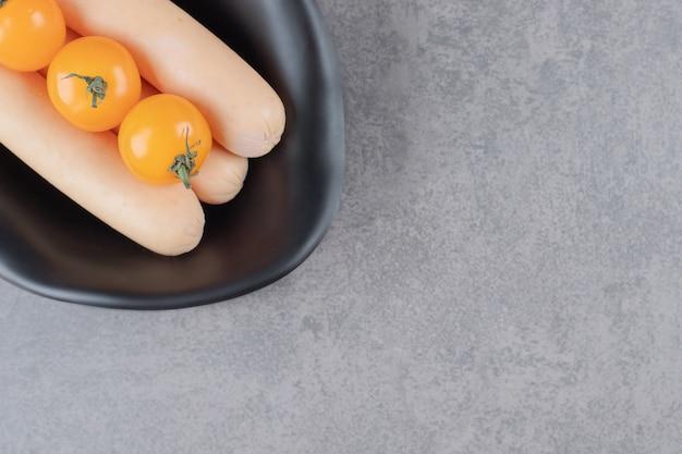 Een zwarte plaat met gekookte worst en gele tomaten