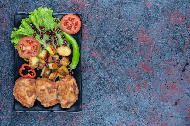 Een zwarte plaat met groenten en kippenkoteletten.