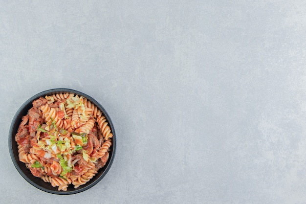 Een zwarte plaat met spiraalvormige pasta met kruiden.