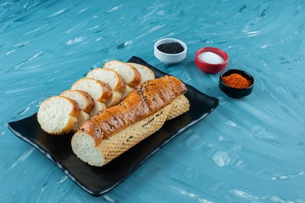 Een zwarte plaat van gesneden witbrood met kruiden op een blauwe achtergrond.