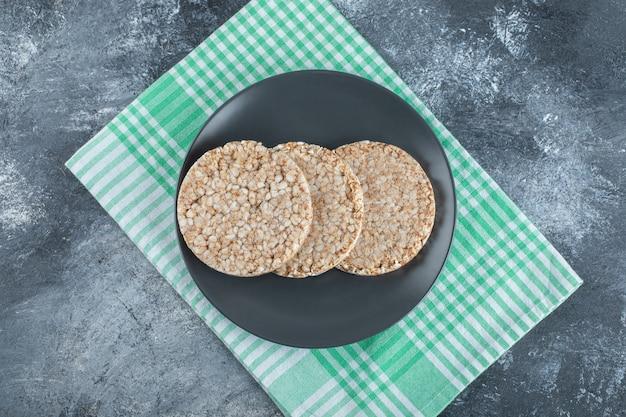 Een zwarte plaat vol knapperig rijstbrood op een tafelkleed.