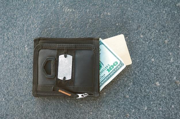 Een zwarte portemonnee met geld en een bankkaart ligt op het asfalt.