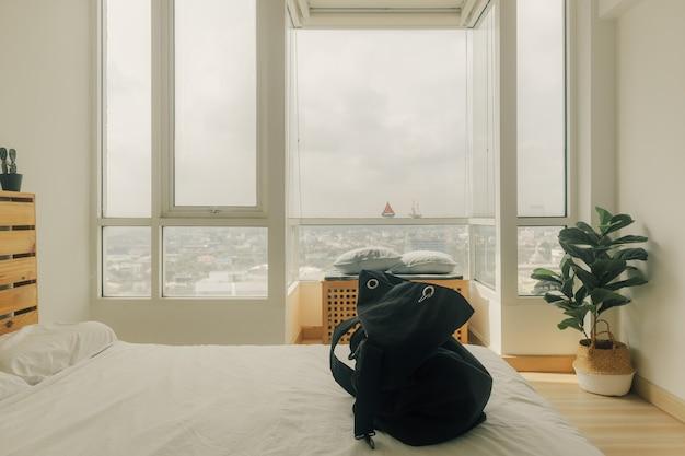Een zwarte rugzak klaarmaken voor een reis in de slaapkamer.