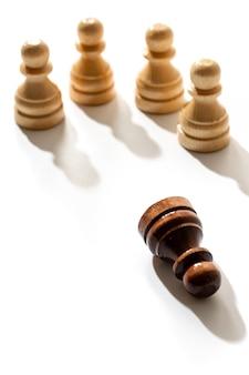 Een zwarte schaakpion die tussen de blanken ligt. concept van racisme en discriminatie.
