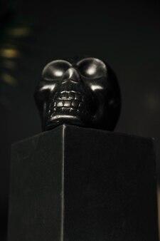 Een zwarte schedel op een zwart podium