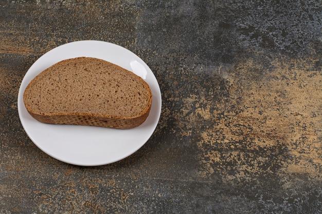 Een zwarte sneetje brood op een witte plaat