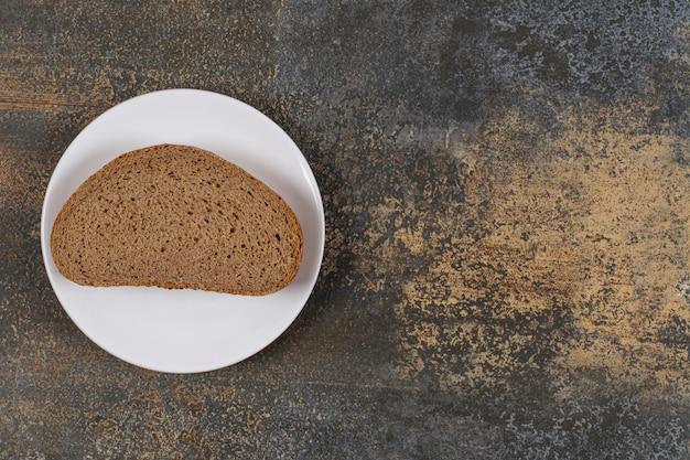 Een zwarte sneetje brood op een witte plaat.