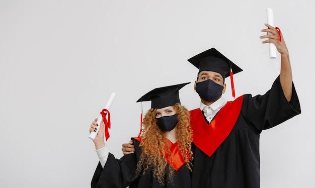 Een zwarte student en een roodharige student pronken met hun langverwachte diploma's in de afstudeerjurk en vierkante pet en een gezichtsmasker van de klas van 2021