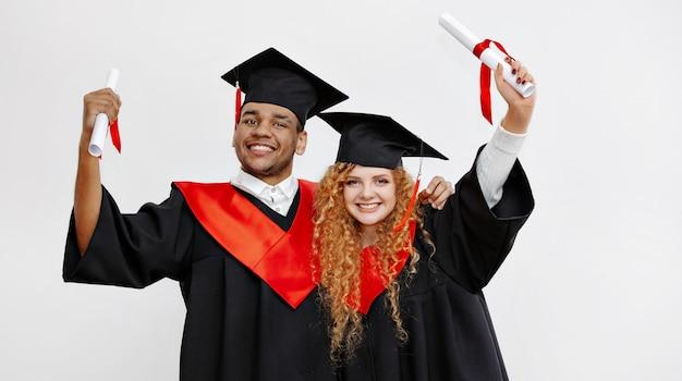 Een zwarte student en een roodharige student pronken met hun langverwachte diploma's in de afstudeerjurk en vierkante pet van de klas van 2021