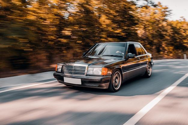 Een zwarte vintage auto rijden op de weg verlangen door het bos.