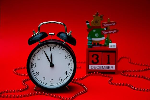 Een zwarte vintage wekker en een rode kerstkalender zijn geïsoleerd op een re