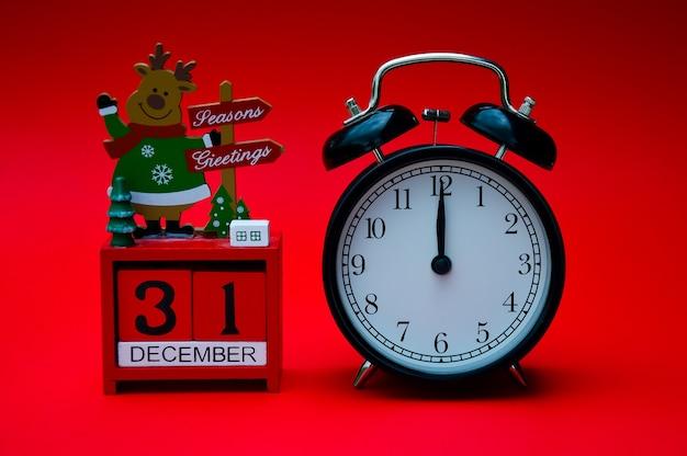 Een zwarte vintage wekker en een rode kerstkalender zijn geïsoleerd op een rode achtergrond
