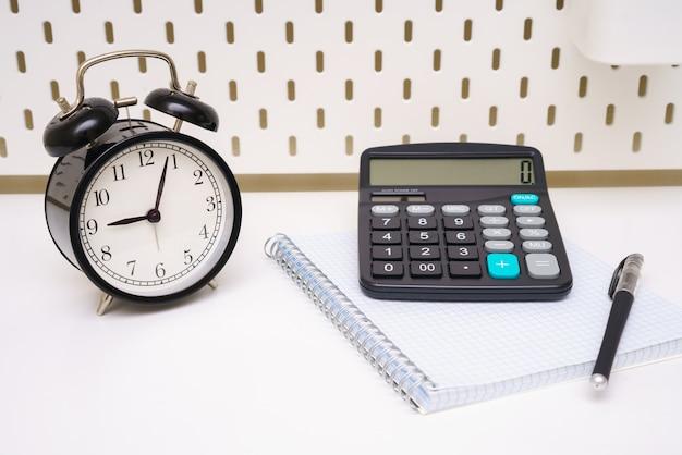 Een zwarte wekker-notitieblokpen en rekenmachine zijn geplaatst op een witte achtergrond van de tafel vijf mi...