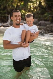 Een zwartharige jonge bebaarde vader houdt zijn kleine kind met een blonde zoon in de armen.