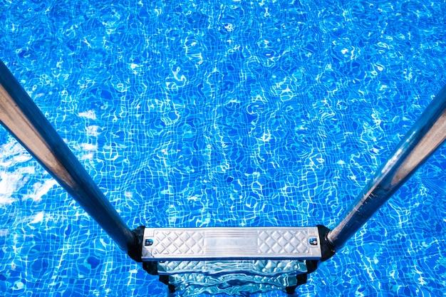 Een zwembad met een metalen ladder om er in te gaan en te baden in de zomer