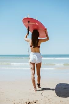 Een zwemmer draagt een surfplank op haar hoofd en gaat naar de oceaanzee, een uitzicht vanaf de achterkant