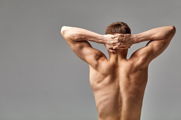Een zwemmer in zwembroek bereidt zich voor op de start, een atleet op een grijze achtergrond bereidt zich voor op een duik, ik poseer voor een duik in het zwembad, draag een bril en een masker, back shot