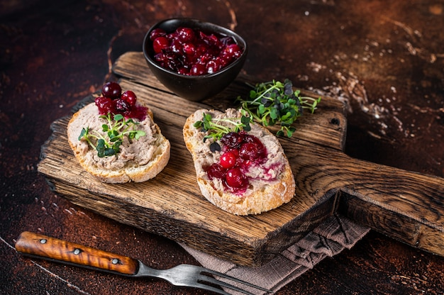 Eend rillettes pate toast met spruitjes op een houten bord. donkere achtergrond. bovenaanzicht.