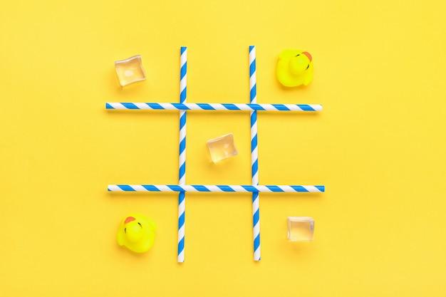Eend speelgoed, ijsblokjes, papieren buisjes met blauwe strepen voor drankjes. zeeslag, tic tac toe spelconcept