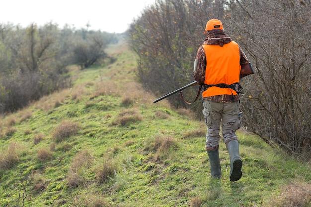 Eendenjager die met jachtgeweer door een weide loopt.