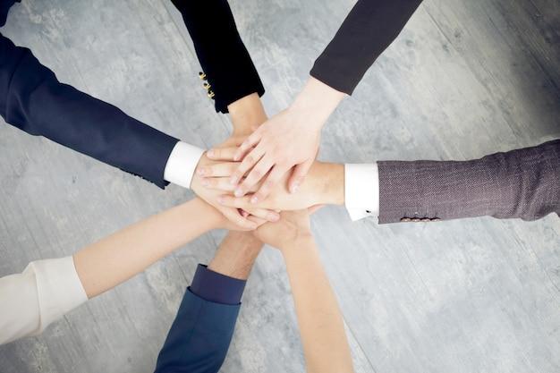 Eenheid en teamwork concept van jonge zakenmensen die hun handen samenvouwen.