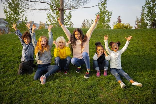 Eenheid. interraciale groep kinderen, meisjes en jongens die samen spelen in het park in de zomerdag. vriendschap kent geen ras. geluk, jeugd, onderwijs, diversiteitsconcept. kijk blij en oprecht.