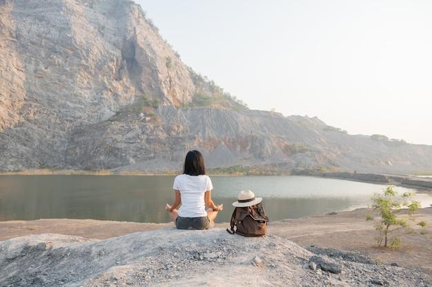 Eenheid met de natuur. jonge vrouw mediteert buiten in de buurt van het meer