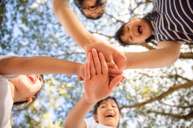Eenheidsconcept. onderaanzicht van kleine kinderen die hun handen in elkaar slaan