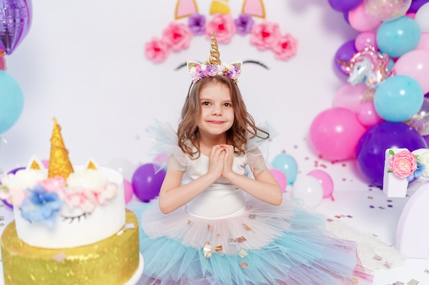Eenhoorn meisje gooit confetti op verjaardagsfeestje