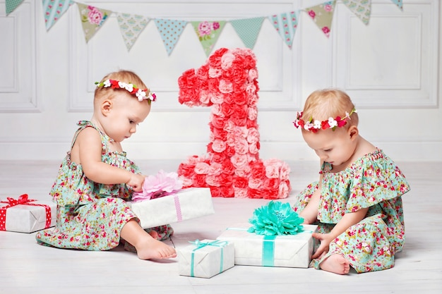 Eenjarige tweeling op de verjaardag.
