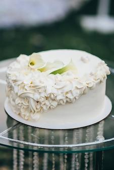 Eenlagige witte bruidstaart versierd met crème in de vorm van bloemen staat op een glazen tafel in de natuur