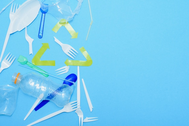 Eenmalig gebruik, wegwerpservies en recyclingsteken op achtergrond. lepels, vorken