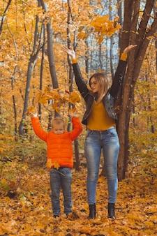 Eenoudergezin speelt met herfstbladeren in het park gelukkige moeder en zoon gooien herfstbladeren erin