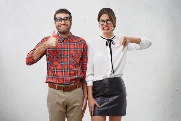 Eens en oneens concept. twee mannelijke en vrouwelijke vrienden drukken verschillende emoties uit terwijl ze iets evalueren.
