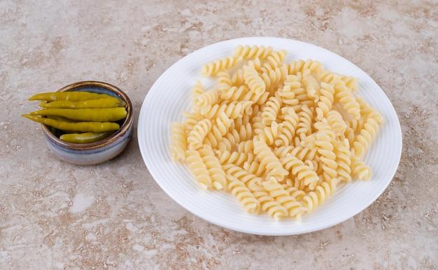 Eenvoudig bord pasta en een kleine kom met ingemaakte paprika's op een marmeren oppervlak.