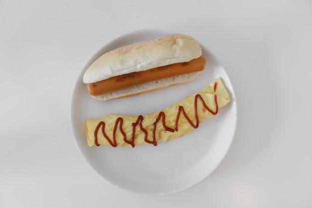 Eenvoudig eenvoudig ontbijt van omelet en worst geserveerd op witte tafel.