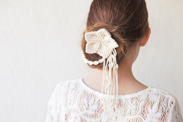 Eenvoudig en elegant kapsel met stijlvolle haaraccessoire trouwstijl op witte achtergrond