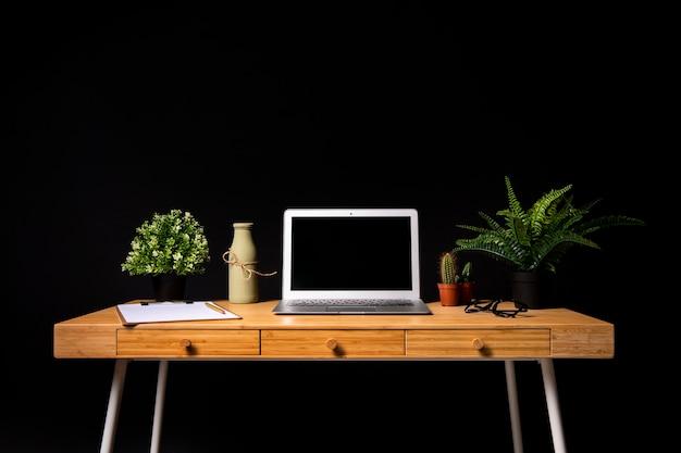Eenvoudig houten bureau met grijze laptop