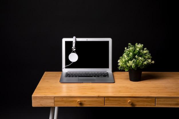 Eenvoudig houten bureau met laptop en plant