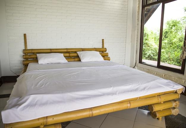 Eenvoudig interieur met houten bed gesloten voor groot raam met bomen buiten.