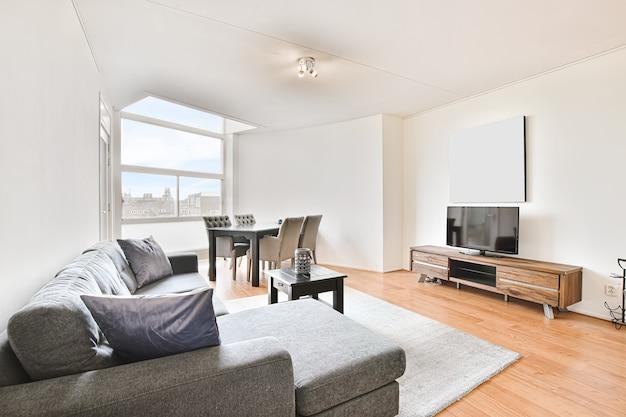 Eenvoudig interieur van lichte woonkamer met grijze bank voor tv en eettafel tegen raam