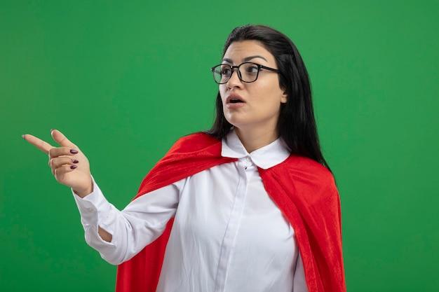 Eenvoudig jong kaukasisch superheromeisje die hand met haar open mond omhoog houden die recht op groene muur kijken
