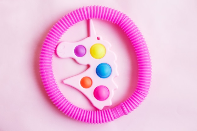 Eenvoudig kuiltje in de vorm van een eenhoorn en een buis fidget speelgoed op een roze achtergrond