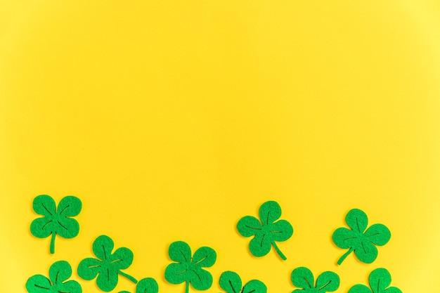 Eenvoudig minimaal ontwerp met de groene bladeren van de klaverklaver die op gele achtergrond worden geïsoleerd
